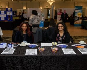 Image: Two women sit behind a black table with brochures laid out.