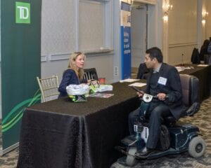 Image: A man using a motorized scooter speaks to a woman sitting at a black table